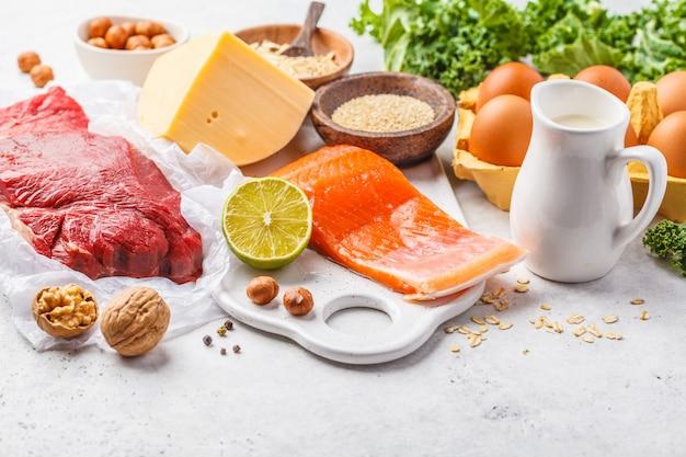 バランスの取れたダイエット食品の背景。タンパク質食品:魚、肉、チーズ、キノア、白い背景の上のナッツ。 Premium写真