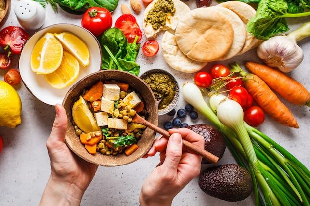 健康的なベジタリアン料理の背景。野菜、ペスト、レンズ豆の豆腐カレー。 Premium写真