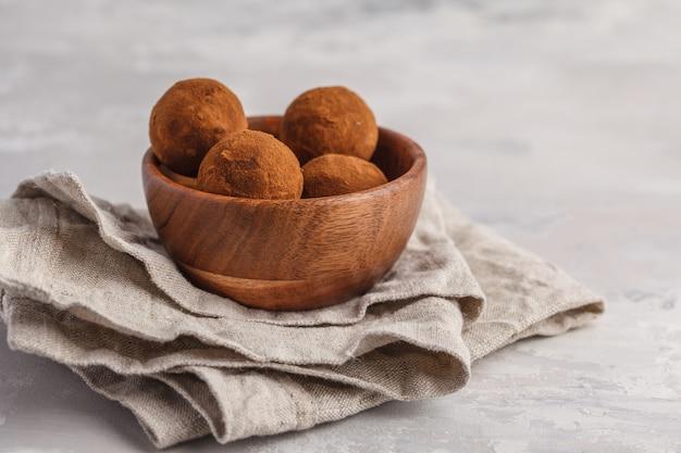 Домашний здоровый веганский сырой энергии трюфель шарики с рожкового дерева в деревянной миске. концепция здорового веганского питания. Premium Фотографии