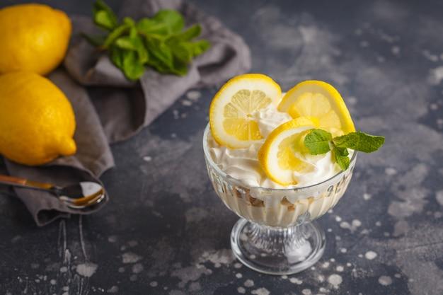 レモンデザートイングリッシュレモンのトライフル、チーズケーキ、ホイップクリーム、パフェ。暗い背景上のガラスのフルーツムース。 Premium写真