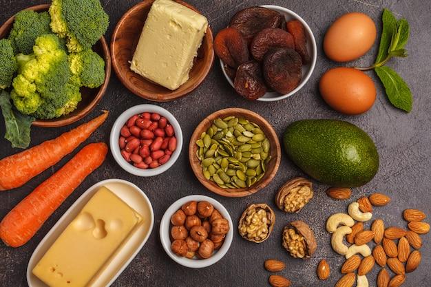 ニンジン、ナッツ、ブロッコリー、バター、チーズ、アボカド、アプリコット、種子、卵。暗い背景、コピースペース Premium写真