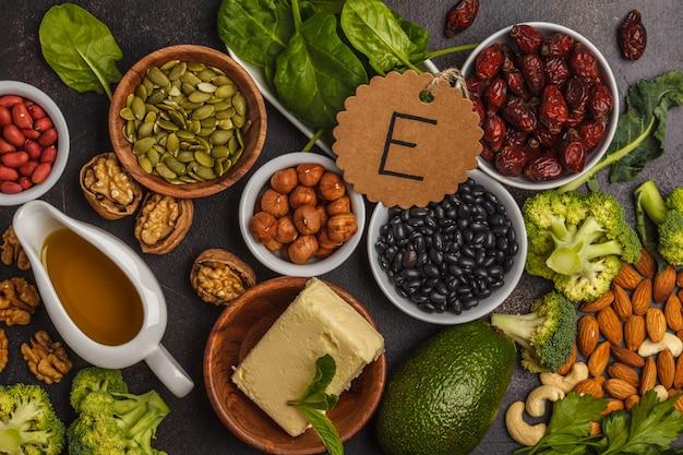 油、ナッツ、アボカド、バター、健康的な脂肪、ローズヒップ、パセリ、種子、ほうれん草。暗い背景、上面図 Premium写真