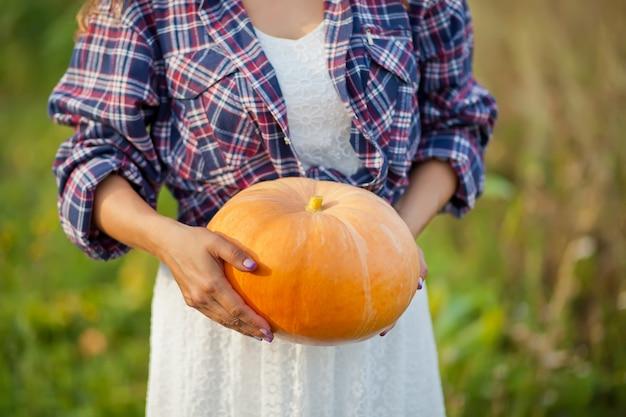 庭で熟したカボチャを持つ女性 Premium写真