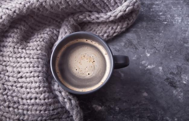 コーヒーと灰色のテーブルにスカーフの灰色のマグカップ。秋のコンセプト。ミニマリズム。 Premium写真