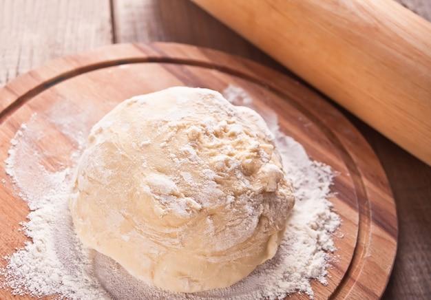 Сырое тесто для пиццы или выпечки хлеба на деревянной разделочной доске на черном фоне Premium Фотографии