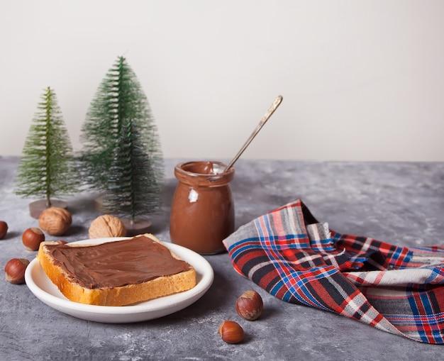Хлебный тост с шоколадно-сливочным маслом, миниатюрные елочные игрушки на бетонном фоне Premium Фотографии