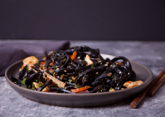 Черные чернила кальмара лапша удон с куриным мясом на черной табличке на темном фоне камня. Premium Фотографии