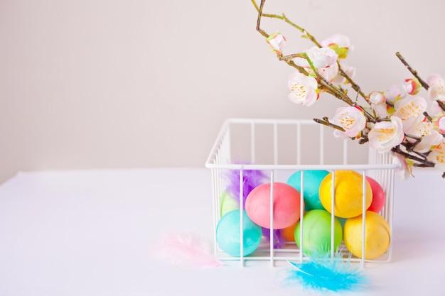バスケットと桜の枝でイースターの日のためのカラフルな卵。コピースペース。 Premium写真