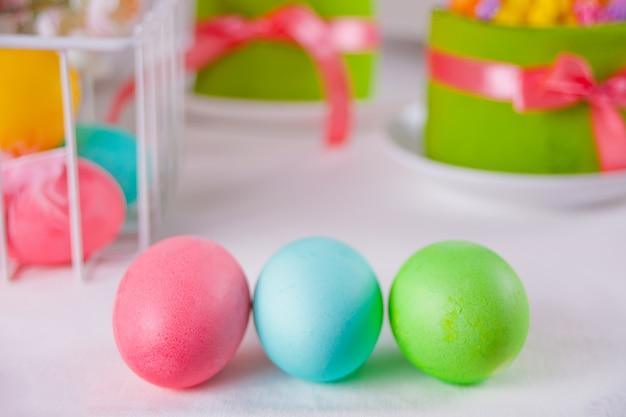 イースターの日、ギフトボックス、小さなケーキのカラフルな卵 Premium写真