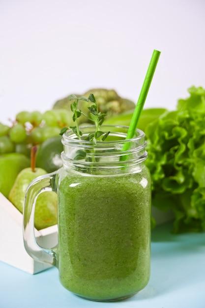果物と野菜のガラスの瓶に新鮮なブレンドグリーンスムージー。健康とデトックスのコンセプトです。 Premium写真