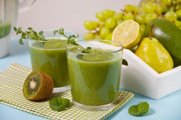 フルーツと野菜のグラスにブレンドした新鮮なグリーンのスムージー。健康とデトックスのコンセプトです。 Premium写真