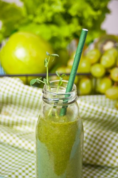 果物と野菜のガラス小瓶に新鮮なブレンドグリーンスムージー。健康とデトックスのコンセプトです。 Premium写真
