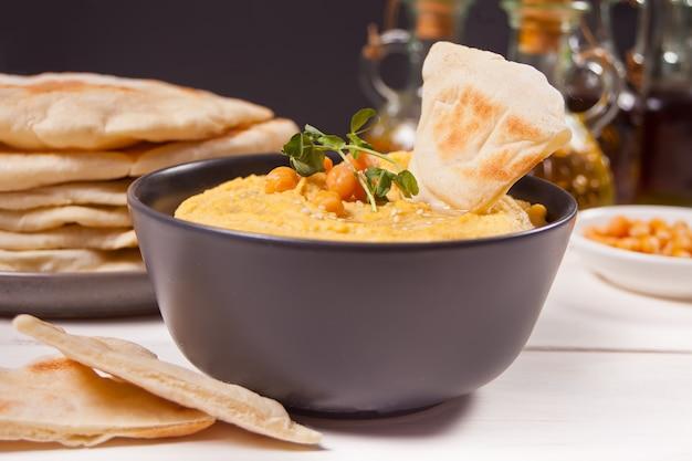 Традиционная закуска хумус с нутом подается со свежим лавашом и зеленью. Premium Фотографии