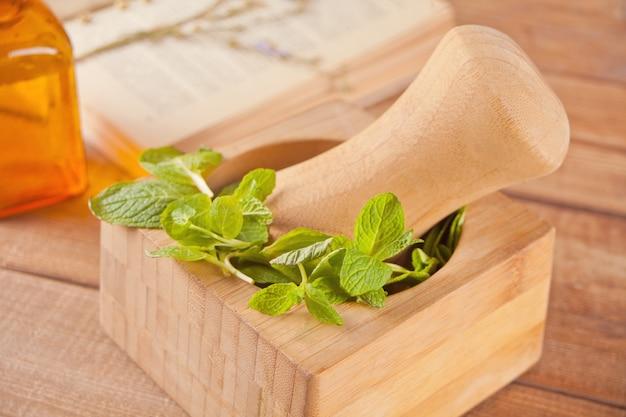 Свежая мята, деревянная ступка, пестик, маленькая бутля с мятным маслом и старая книга на старом столе. Premium Фотографии