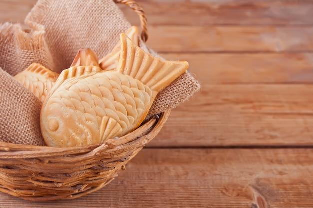 たいやき日本の屋台の食べ物魚の形の甘い充填ワッフル、バスケット Premium写真