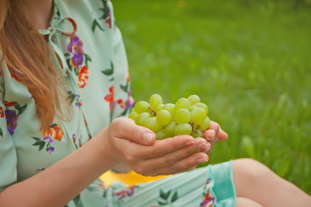 黄色いカバーの上に座って、ブドウの房を持った女性。 Premium写真