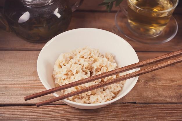 木製の背景にお箸で白いボウルに玄米を調理しました。 Premium写真