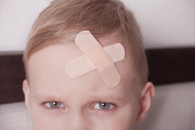 Маленький мальчик с гипсом на голове. закройте Premium Фотографии