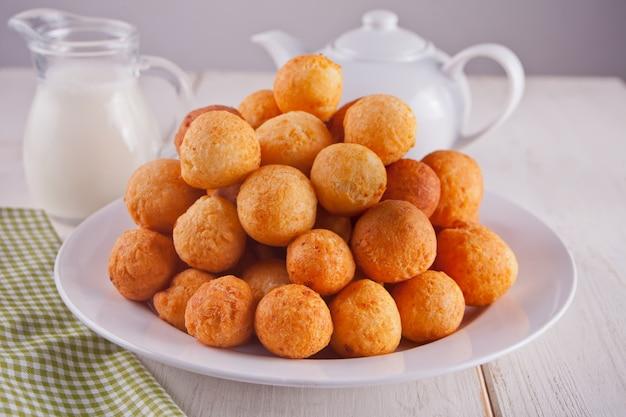 白い背景の上の皿に焼きたての自家製カッテージチーズドーナツの小さなボール。 Premium写真