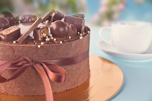 キャンディーと青いテーブルの上のリボンとチョコレートケーキ Premium写真