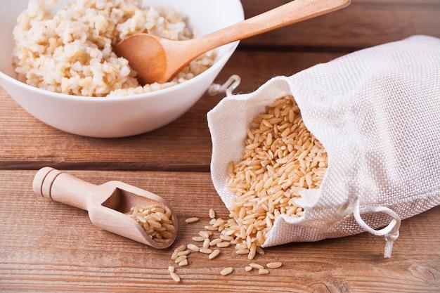 米を袋に入れ、玄米ご飯に白いボウルを Premium写真