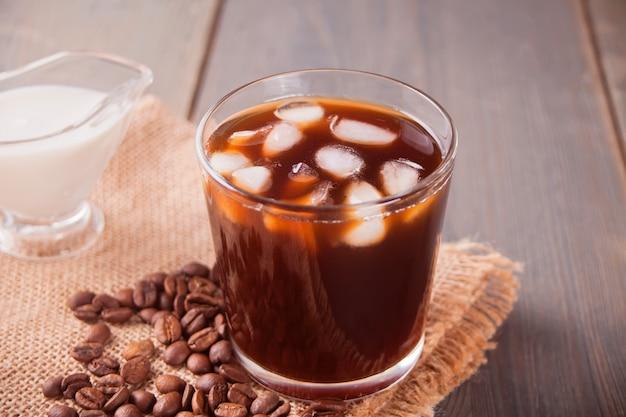 アイスキューブとコーヒー豆のテーブルの上にアイスラテコーヒー。 Premium写真