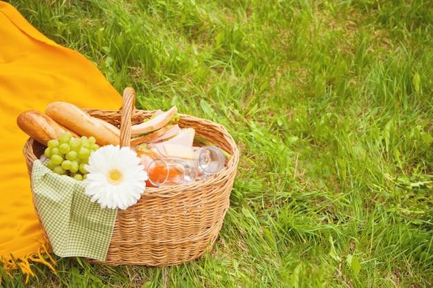 緑の芝生の上の黄色いカバーの上に食べ物、果物、花とピクニックバスケットのクローズアップ Premium写真