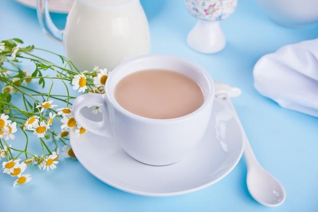 朝。朝ごはん。ミルクティー、ミルクジャー、ブルーの卵 Premium写真