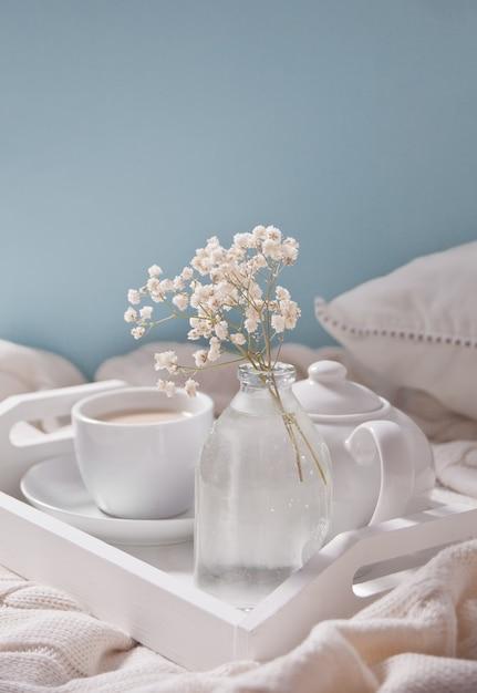 一杯の紅茶、牛乳、ティーポット、白いトレイに白い花の花束のクローズアップ。 Premium写真