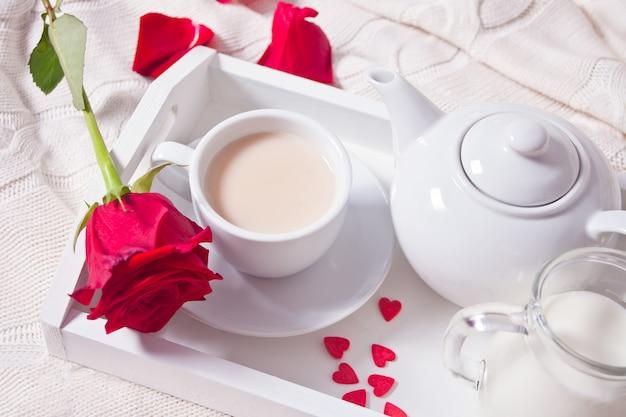 白いトレイに赤いバラと紅茶のカップのクローズアップ Premium写真