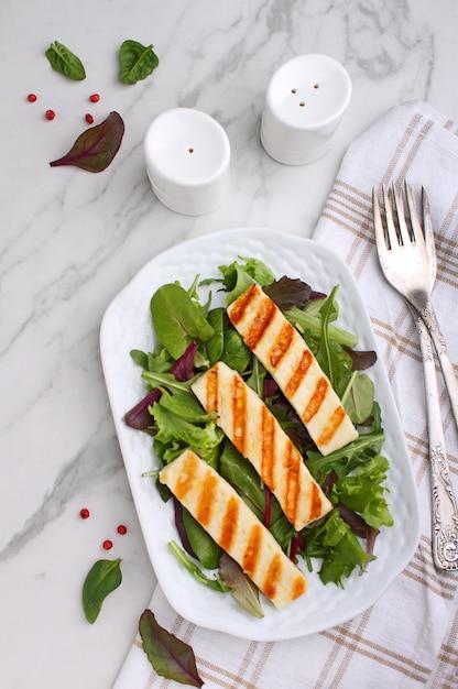 Зеленый салат с жареным сыром халуми в белой тарелке на мраморном столе, вид сверху Premium Фотографии