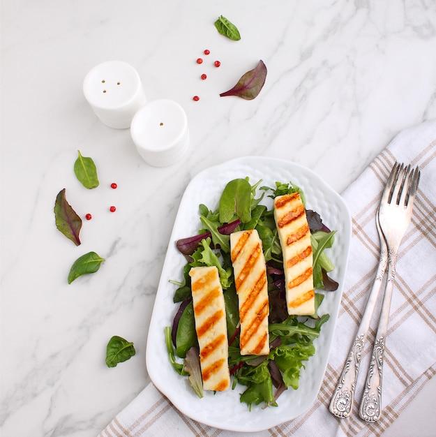 Зеленый салат с жареным сыром халуми на белой тарелке Premium Фотографии