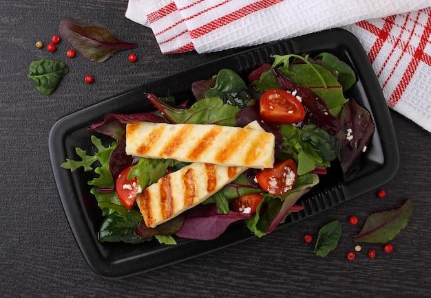 Зеленый салат с жареным сыром халуми на черной тарелке Premium Фотографии