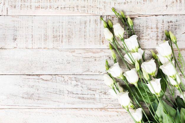 白い花の花束を持つ木製の背景 Premium写真