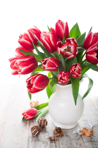 Букет из розовых тюльпанов в вазе на белом фоне Premium Фотографии