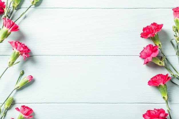 明るいターコイズ色の木製の背景にピンクのカーネーションの花束 Premium写真