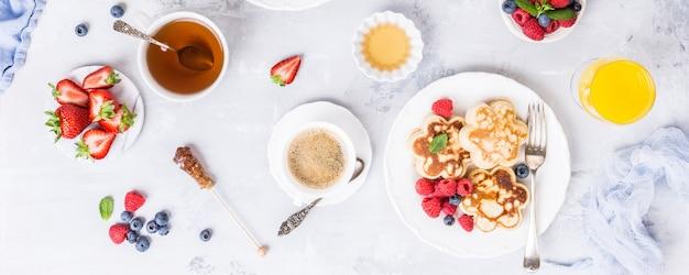 Завтрак с блинчиками в цветочной форме, ягодами и медом на светлом деревянном столе Premium Фотографии