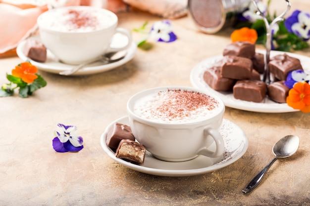 柔らかいヌガーチョコレート菓子とカプチーノのカップ Premium写真