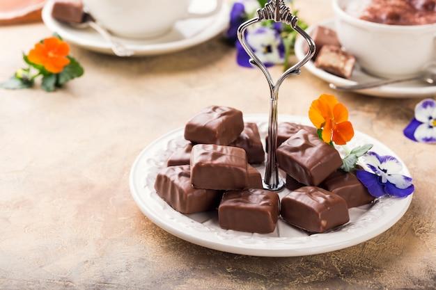 パンジーの花と白い皿の上の柔らかいヌガーチョコレートお菓子。パーティーフードのコンセプトです。 Premium写真