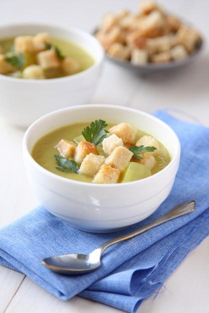 白いボウルにクルトンとパセリのクリーミーなサツマイモのスープ Premium写真