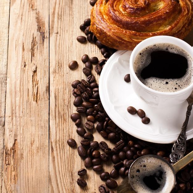 Старый кофейник и чашка на деревянном деревенском фоне Premium Фотографии