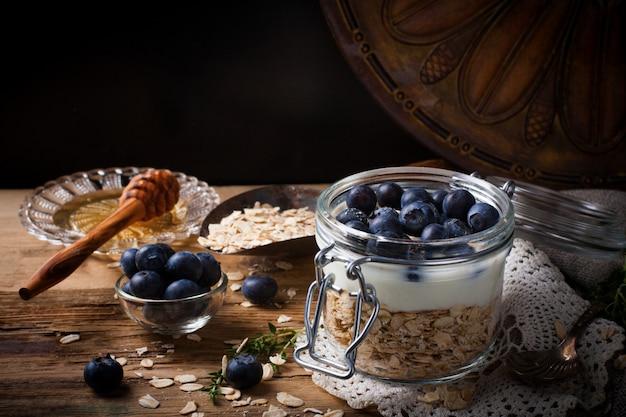 ヨーグルトとガラスの瓶に青い果実のミューズリー。 Premium写真