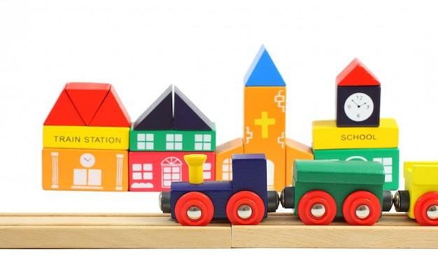 鉄道と白で分離されたおもちゃのブロックで作られた家の木製電車 Premium写真