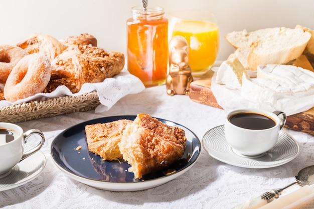 フレンチペストリー、パン、チーズ、コーヒーを含む朝食 Premium写真