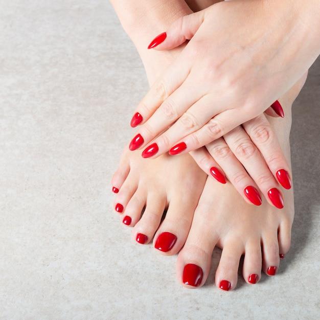 若い女性は彼女の赤いマニキュアの爪を見せています。 Premium写真