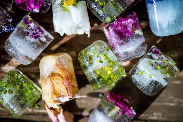 素朴な木製の背景にアイスキューブの冷凍花 Premium写真