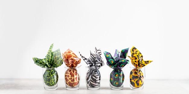 Пасхальные яйца, завернутые в бумагу для печати животных Premium Фотографии