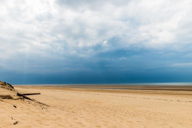 Песчаный пляж формби возле ливерпуля в пасмурный день Premium Фотографии