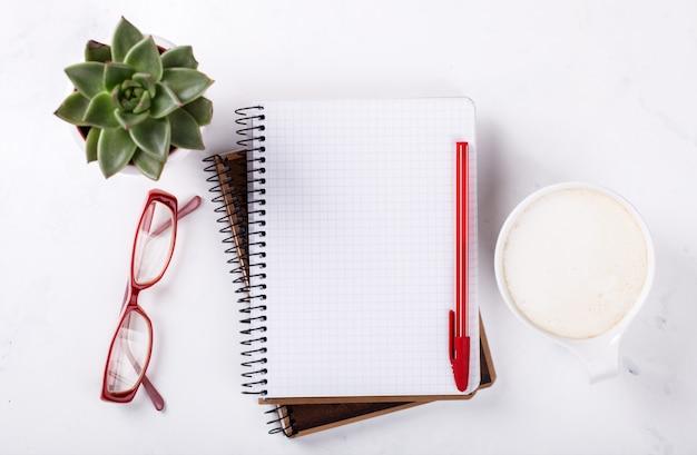 ペン、グラス、コーヒー、花とメモ帳 Premium写真