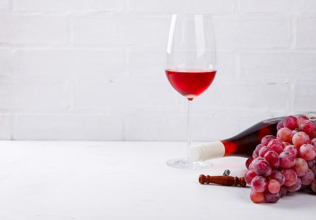 Вино розовое и виноградная гроздь. алкогольный напиток в бокале Premium Фотографии